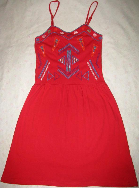 Красное платье с красивым орнаментом на лифе.