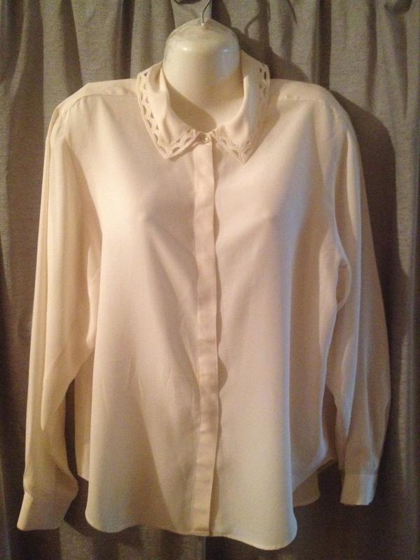 Блузка нежно-бежевого цвета с выбитым воротничком.