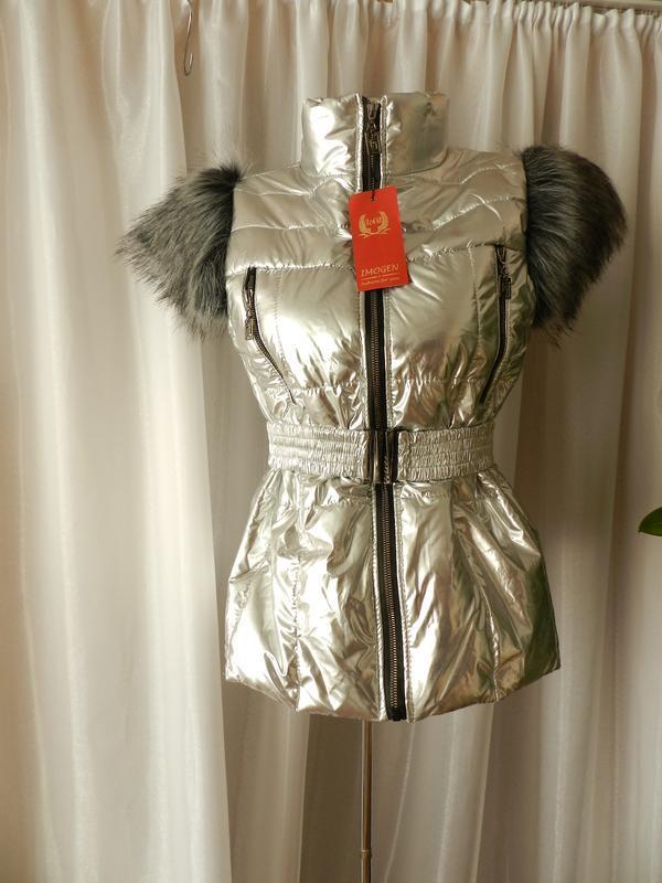 Тёплая блестящая жилетка украшена меховыми плечиками с поясом